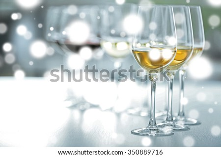 Wineglasses on bright background over snow effect - stock photo