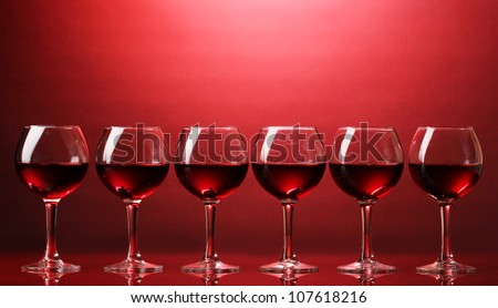 Wineglasses on red background - stock photo