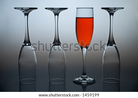 Wineglasses with colored liquid illustrating the concept of possitive thinking. - stock photo