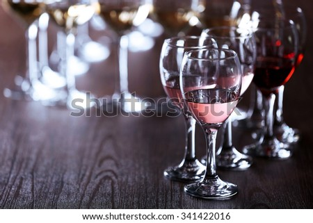 Wineglasses with white, red and pink wine on wooden table close-up