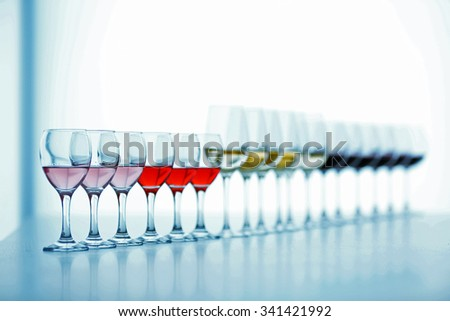 Wineglasses with white, red and pink wine on wooden table on bright background - stock photo