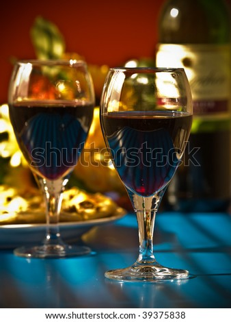 wineglasses with wine and bottle and  food