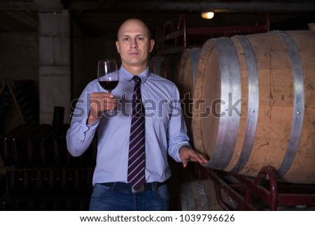 Winemaker inspecting quality of red wine, standing near bottles racks in winery vault