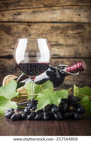 Winery background. Wineglass with bottle of red wine and cluster of grape on wooden table - stock photo
