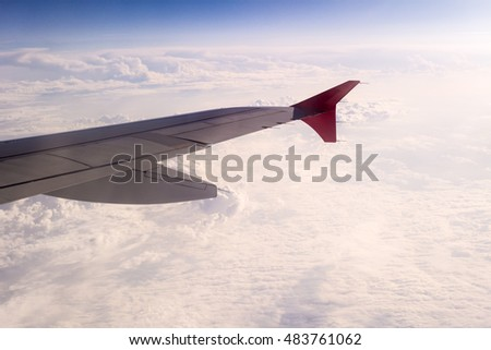 Wing of aircraft with the snow-white clounds on background