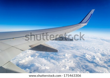 Wing of airplane above clouds in the sky - stock photo