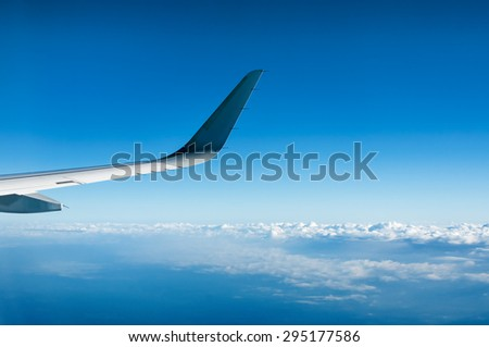 Wing of  airplane  flying above the clouds - stock photo