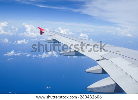 Wing of airplane over the clouds - stock photo