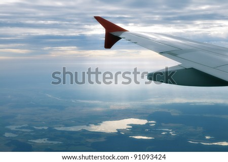 Wing of an airplane and the land below - stock photo