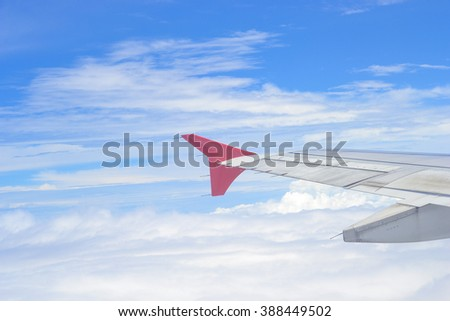 Wing of an airplane flying above the clouds.