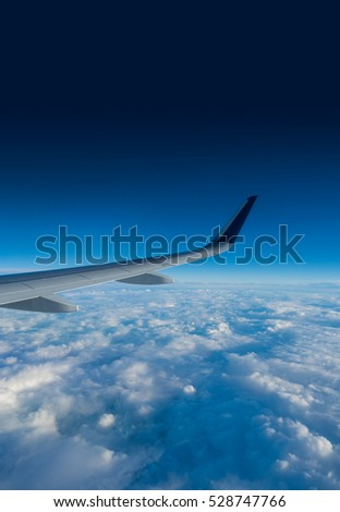 Wing of an airplane flying above the clouds on a clear sunny day