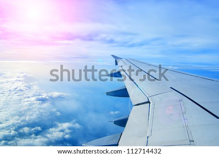 Wing of an airplane flying above the clouds. people look at the sky from the window of the plane, using air transport to travel. back light sun beam - stock photo