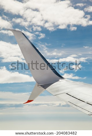 Wing of an airplane flying above the clouds. View from plane win - stock photo