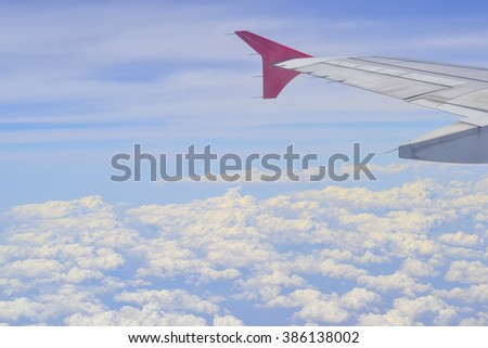 Wing of an airplane over the cloud