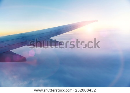 Wing of the plane on blue sky background - stock photo