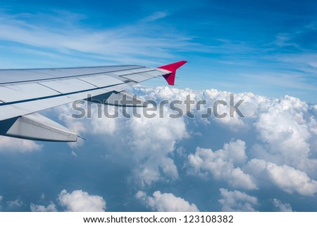 Wing of the plane on sky background - plane wing with cloud patterns - view from the window of a plane of the wing, the sky - View of jet plane wing - stock photo