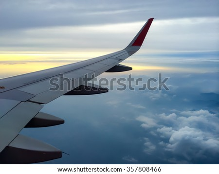 Wing of the plane with cloudy sky on background at sunset - stock photo