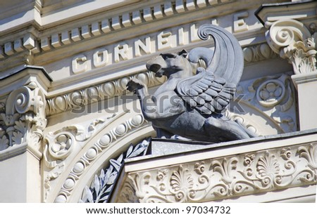 winged griffin stone statue on the pedestal - stock photo