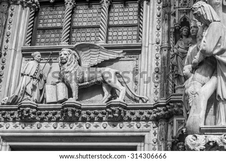Winged lion, symbol of the city, with the Doge, on the Doge's Palace (Palazzo Ducale), San Marco, Venice, Italy. Black and white photography.