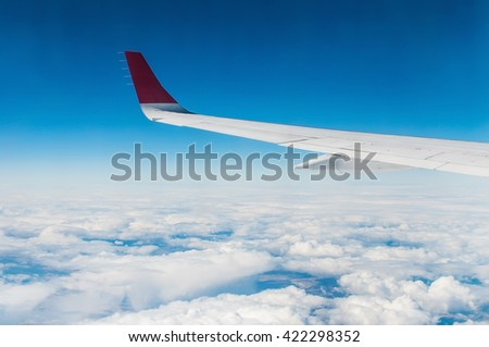 wings of airplane in the sky with cloud in sunny day.