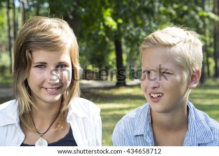Winking boy and smiling girl sitting on the green grass in a nature sunny day. Concept of positive thoughts and emotions.
