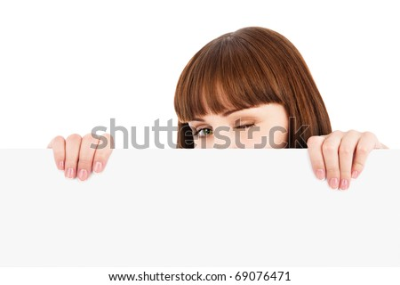 Winking young woman peeking over blank billboard sign isolated on white