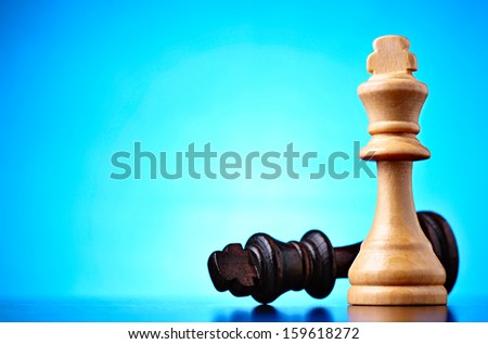 Winner and loser depicted by two chess pieces with the black king lying on its side dominated by the wooden king against a blue background with highlight and copyspace - stock photo