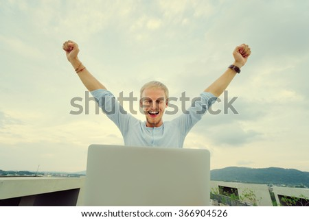 Winner businessman. Young excited man working on laptop while sitting on the roof top. - stock photo