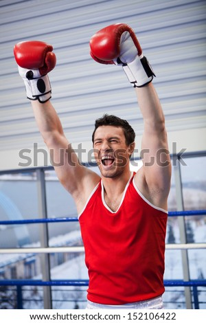 Winner. Cheerful young boxer keeping his arms raised while standing on boxing ring - stock photo