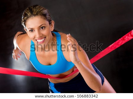 Winner female athlete crossing the finishing line - stock photo