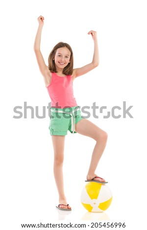 Winner girl with beach ball. Cheering girl in pink shirt and green shorts posing with a beach ball under her foot. Full length studio shot isolated on white. - stock photo