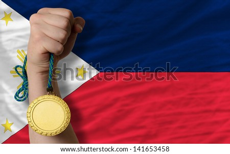 Winner holding gold medal for sport and national flag of philippines