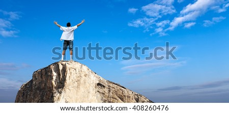 Winner man standing on the top of mountain concept of success