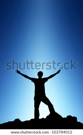 Winner on peak of the mountain. Bright light and dark sky - stock photo