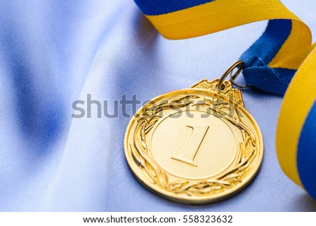 Winners embossed gold medal on a ribbon over blue fabric conceptual of a sporting championship or competition win