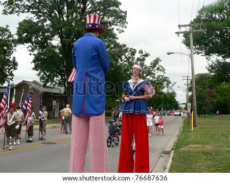 WINNETKA, ILLINOIS-JULY 4: Stilt-walkers dressed as Uncle Sam and Lady Liberty talk at a Fourth of July Parade on July 4, 2007 in WINNETKA, ILLINOIS - stock photo