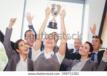 Winning business team with a woman executive holding a gold trophy - stock photo