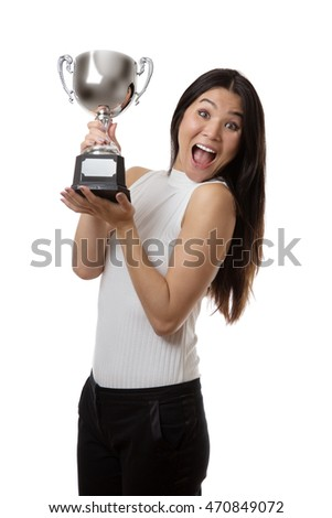 winning business woman holding a large trophy