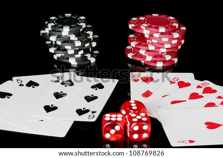 winning combination of playing cards with poker chips and dice on black background