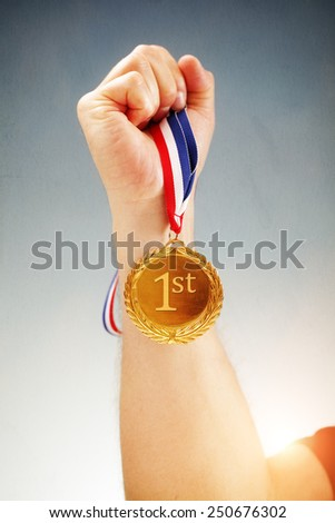 Winning first place hand holding gold medal - stock photo