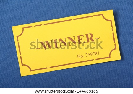 Winning Golden or yellow raffle or lottery ticket on a blue woven material background - stock photo