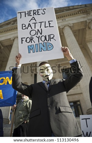 WINNIPEG, CANADA - SEPTEMBER 17: An unidentified protester wearing a Guy Fawkes mask lifts a sign while marking Occupy Wall Street's one year anniversary on September 17, 2012 in Winnipeg. - stock photo
