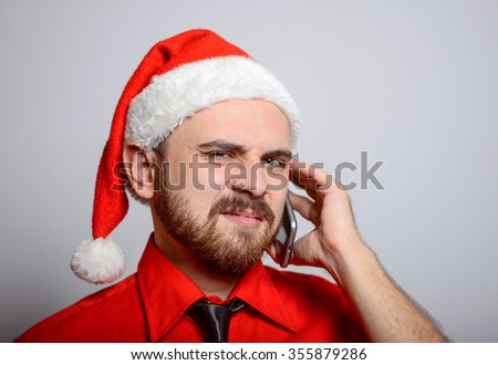 Winter, a business man on the phone says in exasperation. Corporate party, Christmas hat isolated portrait of a man on a gray background, studio photo. - stock photo