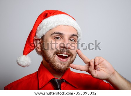 Winter, a business man showing two fingers and smiles. Corporate party, Christmas hat isolated portrait of a man on a gray background, studio photo.