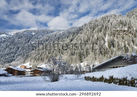 Winter Alpine landscape with mountains and chalets - stock photo