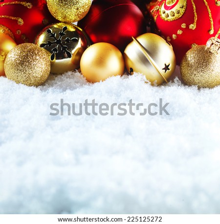 Winter and Christmas background. Beautiful sparkling golden and red Christmas decoration on a white snow background. Ornamental Christmas concept. Close up with copy space. - stock photo