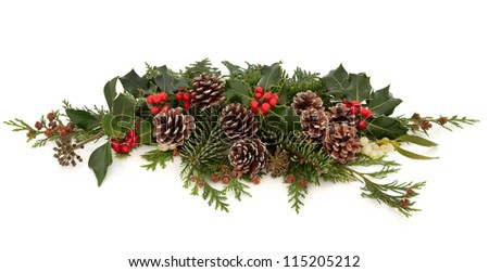 Winter and christmas floral decoration of holly with red berry clusters, mistletoe,  ivy and cedar leaf sprigs with pine cones over white background.