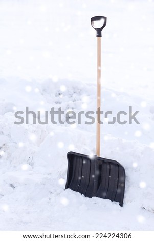 winter and equipment concept - black snowshowel with wooden handle in snow pile - stock photo