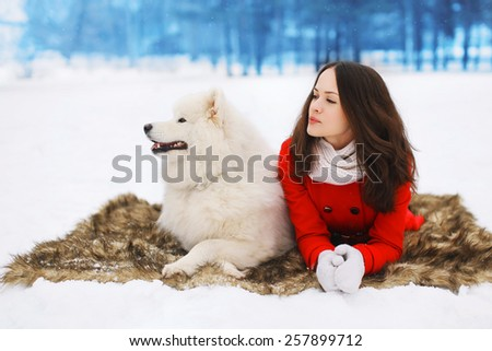 Winter and people concept - beautiful woman with white Samoyed dog on the snow in winter  - stock photo
