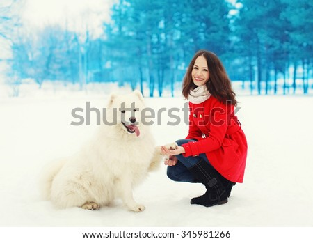 Winter and people concept - happy smiling young woman owner having fun with white Samoyed dog outdoors on snow - stock photo